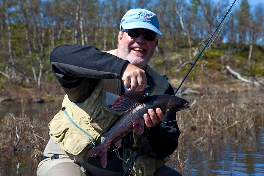 Hans van Klinken shows his large grayling in spawning colors from the Hodalen Lakes in Norway